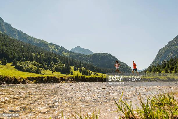 Austria, Tyrol, Tannheim Valley, young couple jogging at riverside