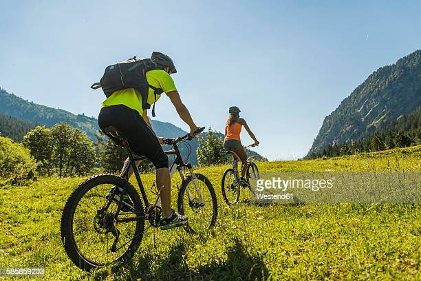 Austria, Tyrol, Tannheim Valley, young couple on mountain bikes in alpine landscape