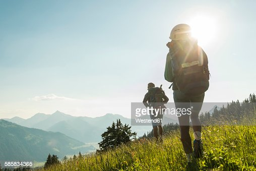 Austria, Tyrol, Tannheimer Tal, young couple hiking on alpine meadow in backlight