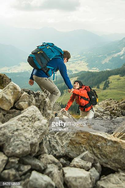 Austria, Tyrol, Tannheimer Tal, young couple hiking on rocks