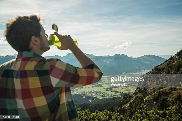Austria, Tyrol, Tannheimer Tal, young man drinking water in mountainscape