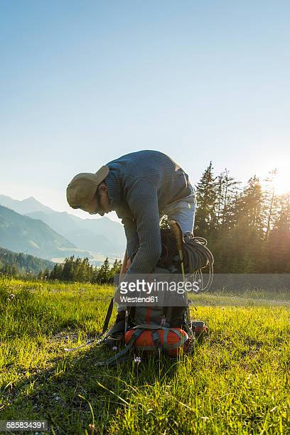 Austria, Tyrol, Tannheimer Tal, young man packing his backpack on alpine meadow