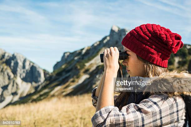 Austria, Tyrol, Tannheimer Tal, young woman looking through binocular