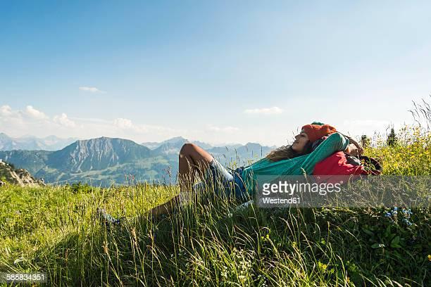 Austria, Tyrol, Tannheimer Tal, young woman lying on alpine meadow