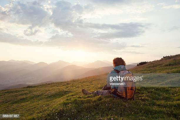 Austria, Tyrol, Unterberghorn, hiker resting in alpine landscape at sunrise