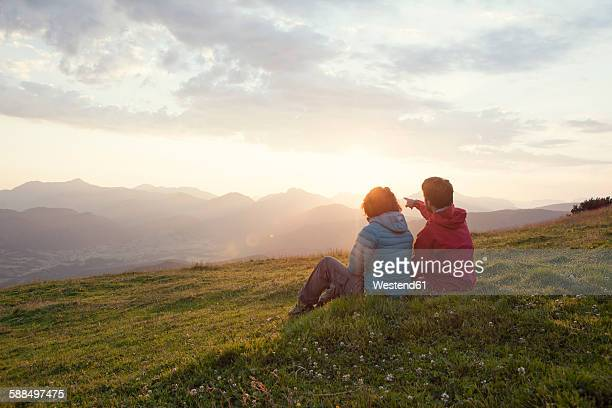 Austria, Tyrol, Unterberghorn, two hikers resting in alpine landscape at sunrise