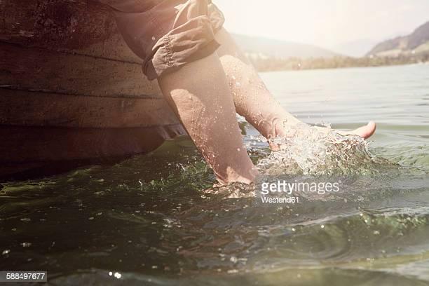 Austria, Tyrol, womans feet splashing in water of Walchsee