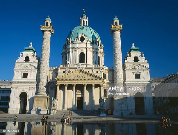 Austria Vienna Karlskirche aka Church of St Charles Borromaeus View of the facade showing twin columns and domed roof with pool in the foreground