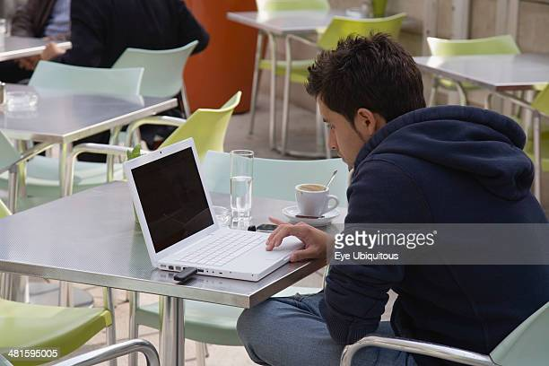 Austria Vienna Neubau District Young man having coffee while surfing the net on laptop at the Museum of Modern Art Museum Moderner Kunst Stiftung...