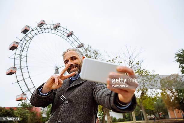Austria, Vienna, portrait of smiling businessman taking a selfie at Prater
