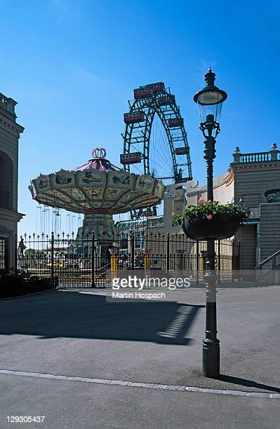Austria, Vienna, Prater park amusement park rides with lamp post in foreground