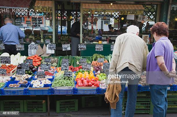 Austria Vienna The Naschmarkt Customers selecting fresh fruit from display on stall that includes aubergines mushrooms peppers and carrots