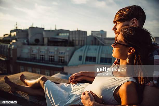 Austria, Vienna, Young couple enjoying romantic sunset on rooftop terrace