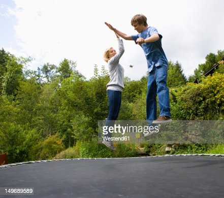 Austria, Young man and woman jumping on trampoline