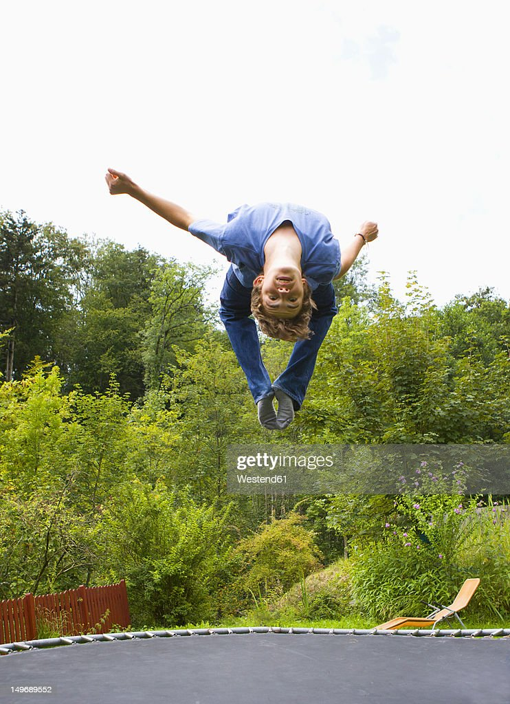Austria, Young man jumping on trampoline