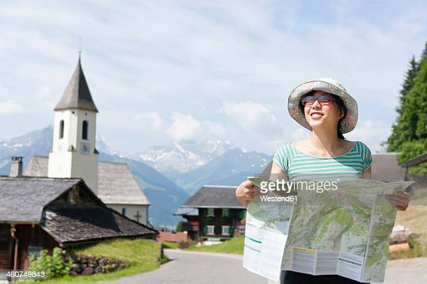 Austria, Young woman holding hiking map, smiling