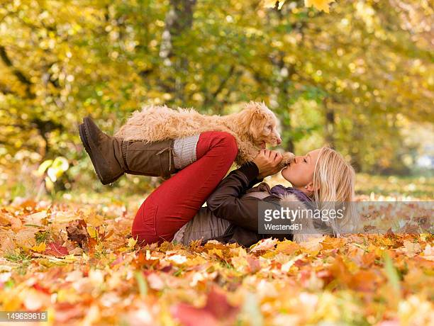 Austria, Young woman playing dog on autumn leaf