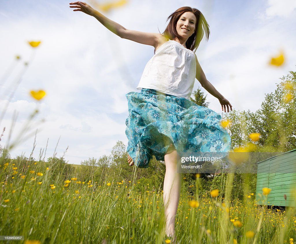 Austria, Young woman running in field of flowers : Stock-Foto