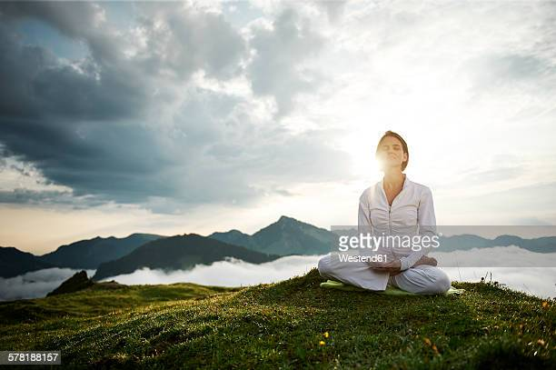Austria.Kranzhorn, Mid adult woman practising yoga on mountain top