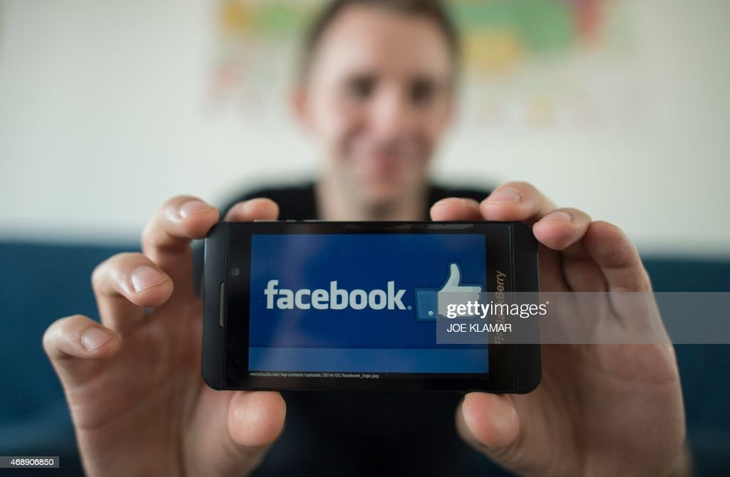 Austrian activist Max Schrems displays a logo of social platform Facebook with his smartphone during an interview with AFP in Vienna Austria on April...