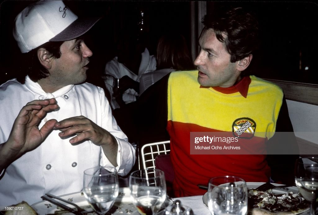 Austrian actor <a gi-track='captionPersonalityLinkClicked' href=/galleries/search?phrase=Helmut+Berger&family=editorial&specificpeople=1670005 ng-click='$event.stopPropagation()'>Helmut Berger</a> is joined at his table by celebrity chef <a gi-track='captionPersonalityLinkClicked' href=/galleries/search?phrase=Wolfgang+Puck&family=editorial&specificpeople=157523 ng-click='$event.stopPropagation()'>Wolfgang Puck</a> at his restaurant 'Spago' in November, 1983 in Los Angeles, California.