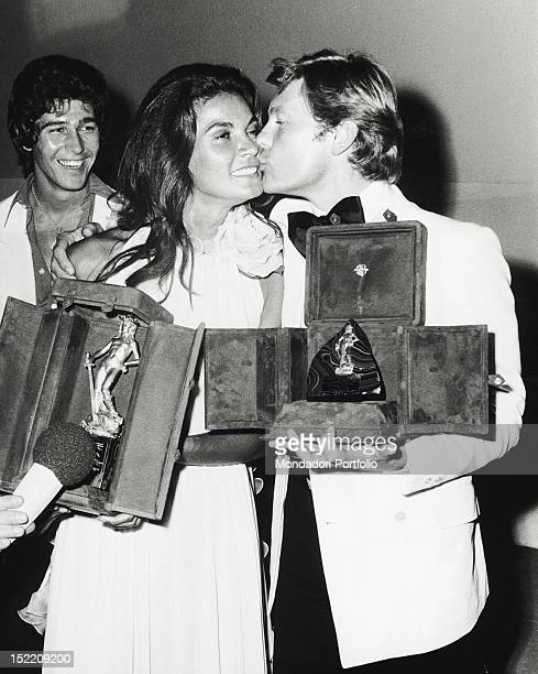 Austrian actor Helmut Berger kissing the David di Donatellowinning Brazilian actress Florinda Bolkan in front of American actor Ryan O'Neal Taormina...