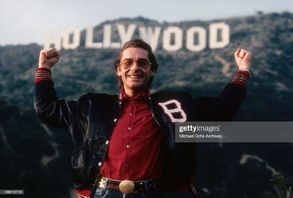 Austrian actor Helmut Berger poses for a portrait under the Hollywood sign in February, 1984 in Los Angeles, California.