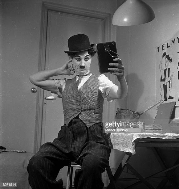 Austrian actress and impersonator Telmy Talia checks her makeup after her uncanny transformation into Charlie Chaplin for a Paris nightclub show