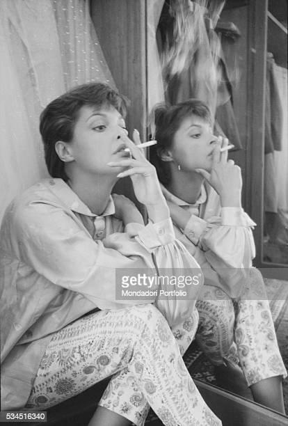 Austrian actress Nadja Tiller smoking beside a mirror during the 19th Venice International Film Festival Venice August 1958