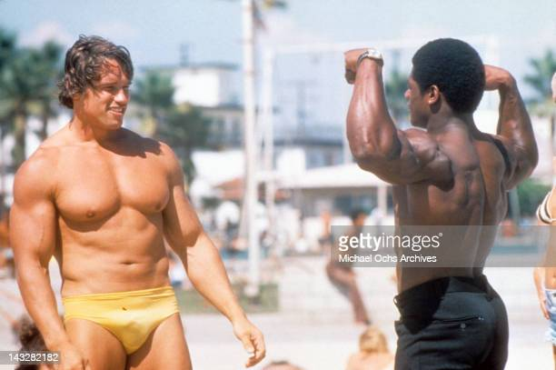 Austrian Bodybuilder Arnold Schwarzenegger admires another bodybuilder at Muscle Beach in Venice in August 1977 in Los Angeles California