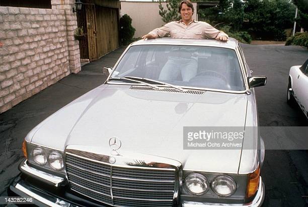 Austrian Bodybuilder Arnold Schwarzenegger poses for a photo standing in his Mercedes circa 1977 in Los Angeles California