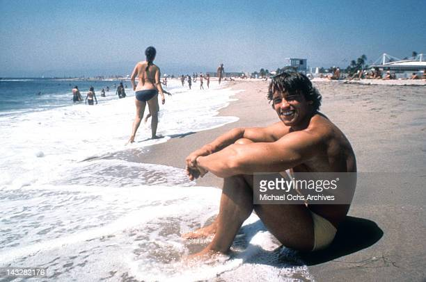 Austrian Bodybuilder Arnold Schwarzenegger sits in the surf on Venice Beach in August 1977 in Los Angeles California
