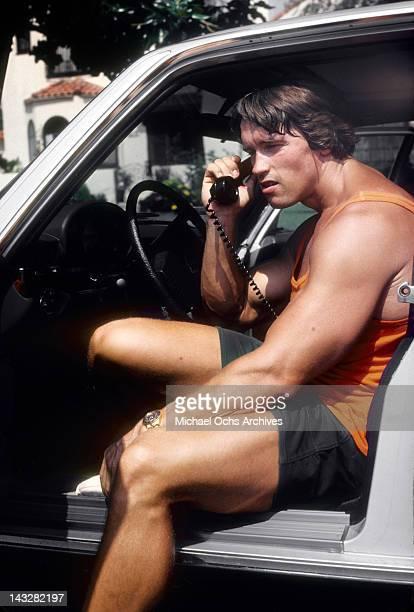 Austrian Bodybuilder Arnold Schwarzenegger talks on his car phone in August 1977 in Los Angeles California