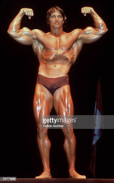 Austrian born actor and former bodybuilder Arnold Schwarzenegger poses in a bathing suit and flexes his muscles in a bodybuilding pose circa 1980...