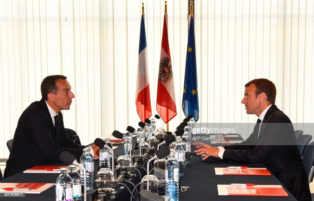Austrian chancellor Christian Kern (L) and French President Emmanuel Macron hold a meeting on August 23, 2017 at the Congress palace in Salzburg. / AFP PHOTO / AFP PHOTO AND POOL / Bertrand GUAY