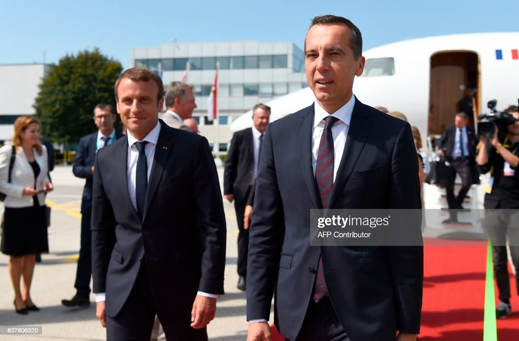 Austrian chancellor Christian Kern (R) walks next to French President Emmanuel Macron upon arrival on August 23, 2017 at the airport in Salzburg. / AFP PHOTO / AFP PHOTO AND POOL / Bertrand GUAY
