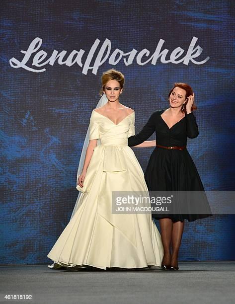 Austrian designer Lena Hoschek walks with a model displaying her fashion at the MercedesBenz Fashion Week in Berlin on January 20 2015 AFP PHOTO /...