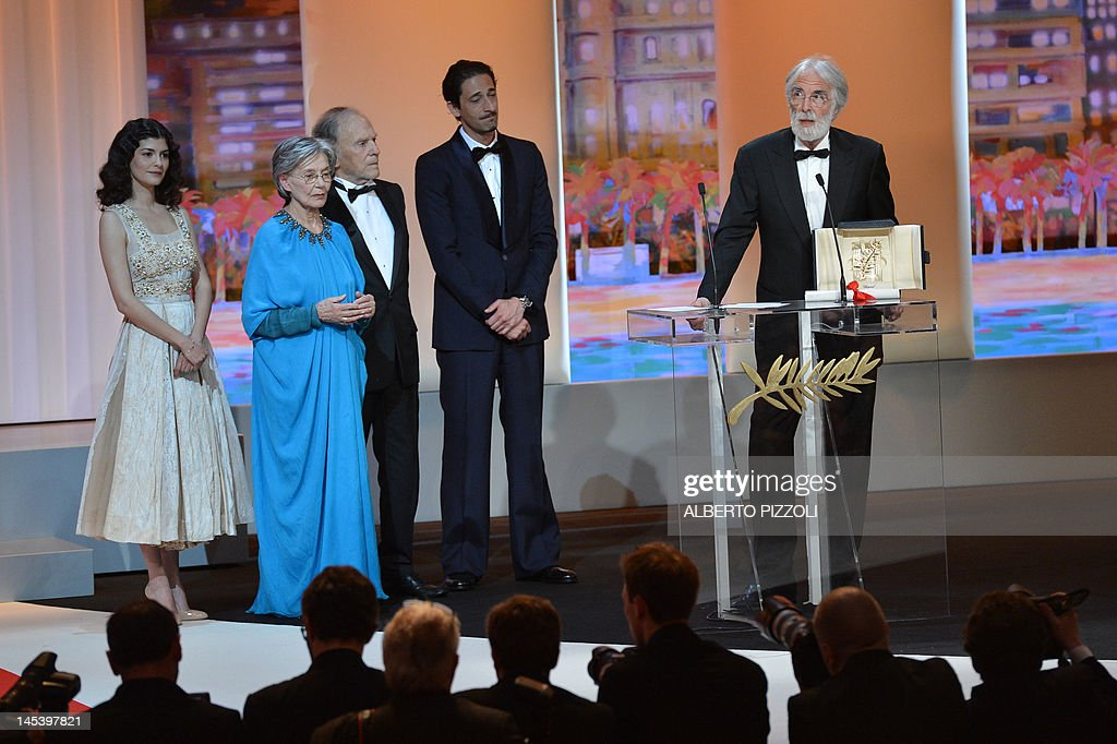 Austrian director Michael Haneke (R) delivers a speech on stage next to French actresses Audrey Tautou (L), Emmanuelle Riva (2ndL), French actor Jean-Louis Trintignant (3rdL) and US actor Adrien Brody after being awarded with the Palme d'Or for his film 'Reality' during the closing ceremony of the 65th Cannes film festival on May 27, 2012 in Cannes. AFP PHOTO / ALBERTO PIZZOLI