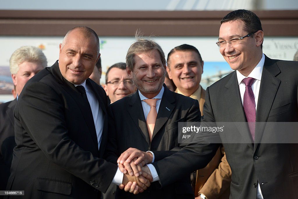 Austrian European Commissioner for regional politics, Johannes Hahn (C) shakes hands with Bulgaria's Prime Minister Boyko Borisov (L) and the Romania's Prime Minister Victor Ponta (R) during an inspection of the construction of the Calafat-Vidin bridge on Danube river between Bulgaria and Romania on October 24, 2012. AFP PHOTO / DIMITAR DILKOFF