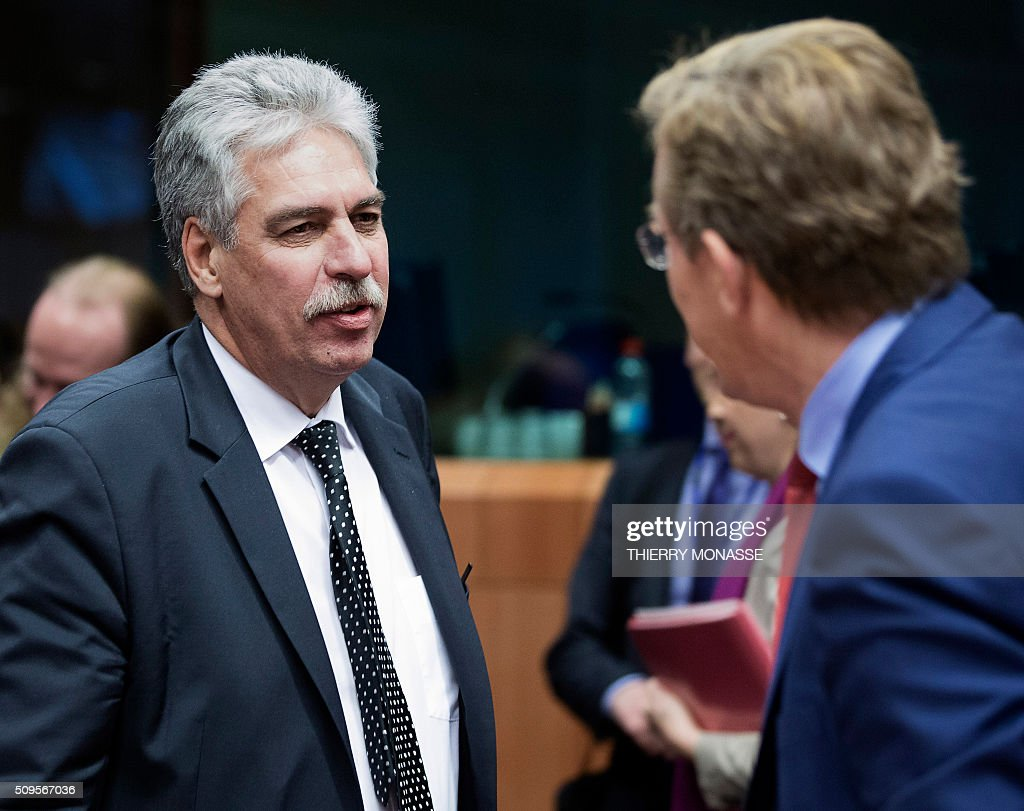 Austrian Finance Minister Hans Jörg Schelling (L) talks to the Belgian Finance Minister Johan Van Overtveldt (R) prior to a meeting of Eurogroup ministers at the European Council headquarters in Brussels on February 11, 2016. / AFP / THIERRY MONASSE