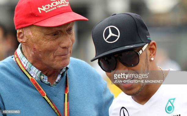 Austrian former formula one racing driver Niki Lauda stands next to Mercedes' British driver Lewis Hamilton at the Monaco street circuit during the...