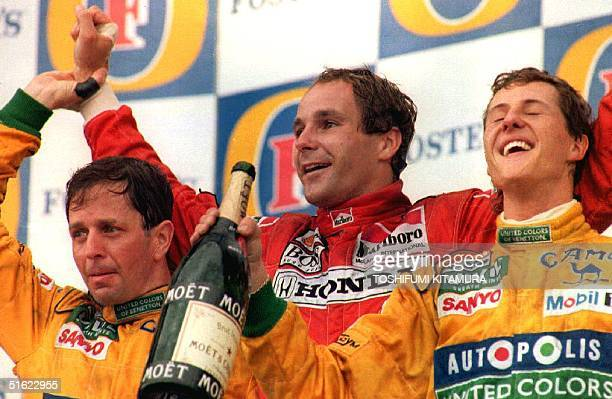 Austrian Formula One driver Gerhard Berger celebrates his victory with German driver Michael Schumacher who placed second and British driver Martin...