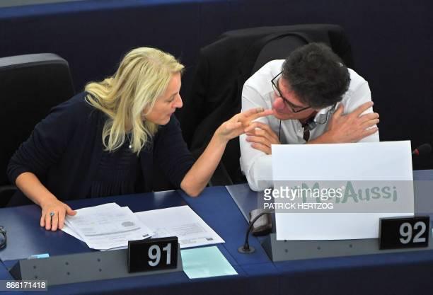 Austrian member of the European Parliament Evelyn Regner and French member of the European Parliament Patrick Durand talk behind a placard reading...