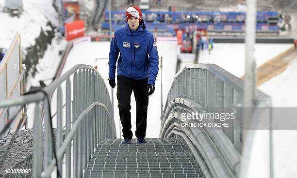 Austrian Michael Hayboeck walks beside the jumping hill ahead the training for the men normal hill individual jump of the FIS Nordic Ski...