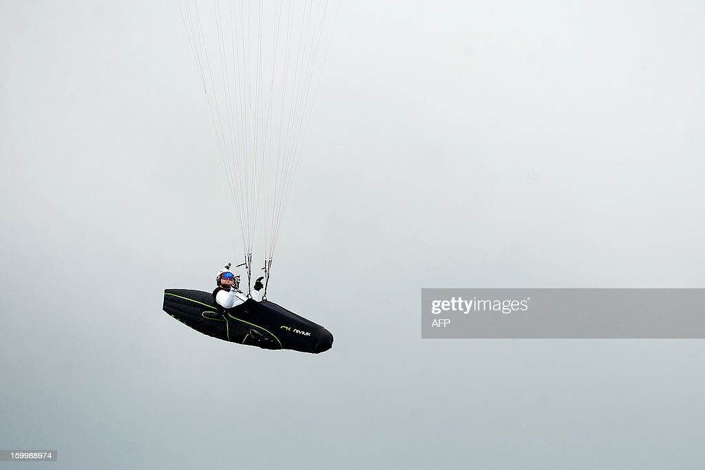 Austrian paraglider pilot Herman Stockl is seen flying in the mountains in Roldanillo, Valle del Cauca department, Colombia, during the Paragliding World Cup Superfinal, on January 24, 2013. The competition is taking place for the first time in Colombia and involves the 140 world's best pilots from 32 countries. AFP PHOTO / Luis ROBAYO
