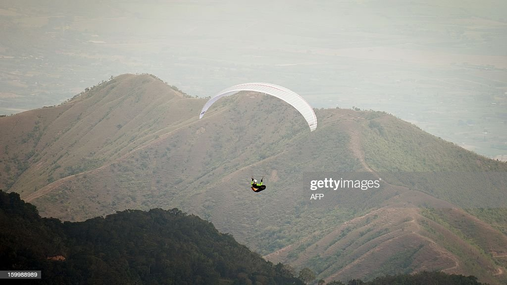Austrian paraglider pilot Othmar Dickbauer flies above the mountains in Roldanillo, Valle del Cauca department, Colombia, during the Paragliding World Cup Superfinal, on January 24, 2013. The competition is taking place for the first time in Colombia and involves the 140 world's best pilots from 32 countries. AFP PHOTO / Luis ROBAYO