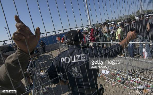 Austrian police officer stands in front of migrants who wait to enter busses at a former truck custom station at the Austrian side of the...