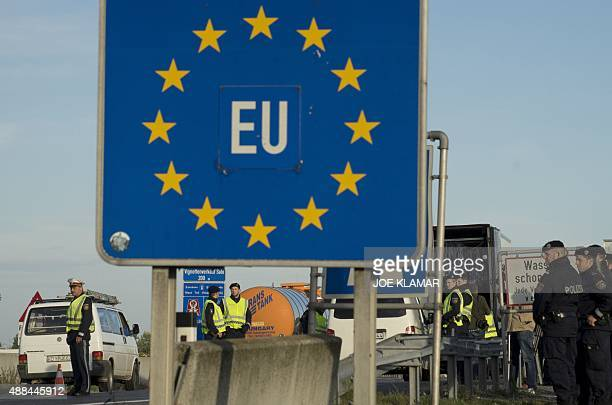 Austrian police officers attend border controls on the Highway A4 near Nickelsdorf at the AustrianHungarian border crossing in early hours on...