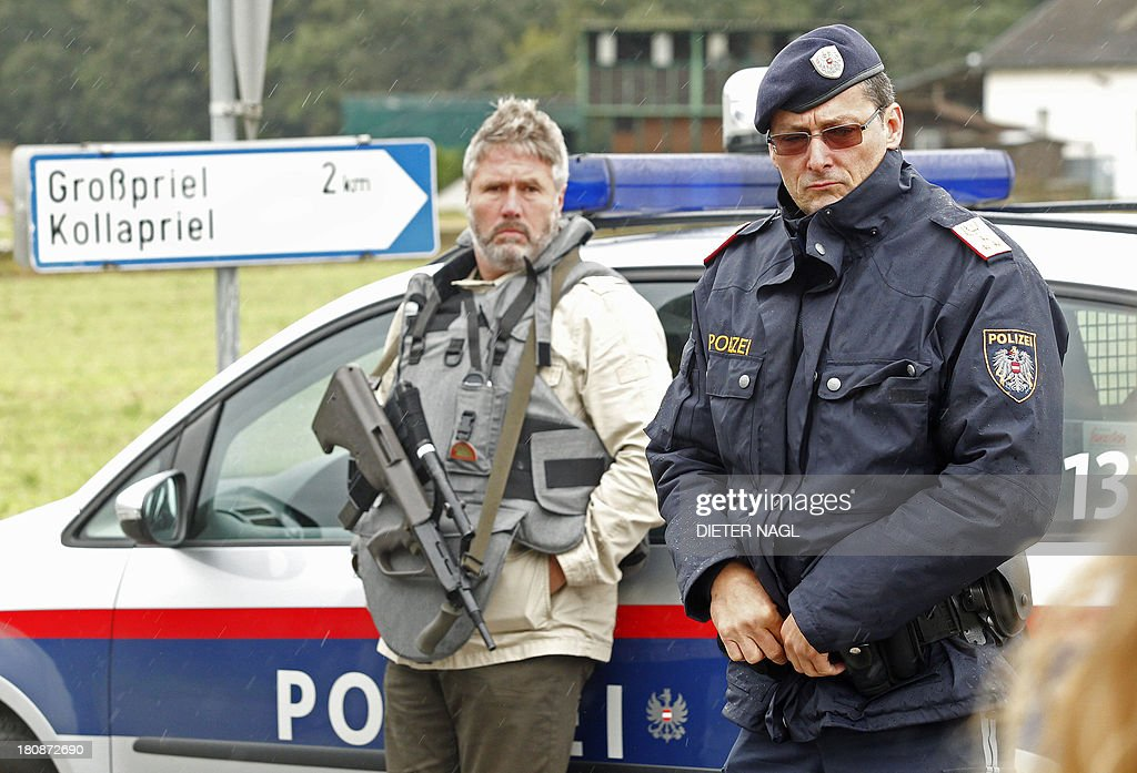 Austrian police officiers block a road on September 17, 2013 near Grosspriel where a poacher has shut himself in a farmhouse with a hostage. Police had attempted to stop the man in his car late on September 16, 2013 near Annaberg, some 100 kilometres (60 miles) west of Vienna, but he shot dead two police officers and an emergency worker and has taken another officer hostage on his run, reports said.