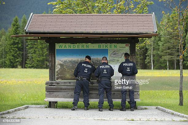 Austrian policemen look at a hiker's map near a police checkpoint on a road leading to the InteralpenHotel Tirol venue of the upcoming Bilderberg...